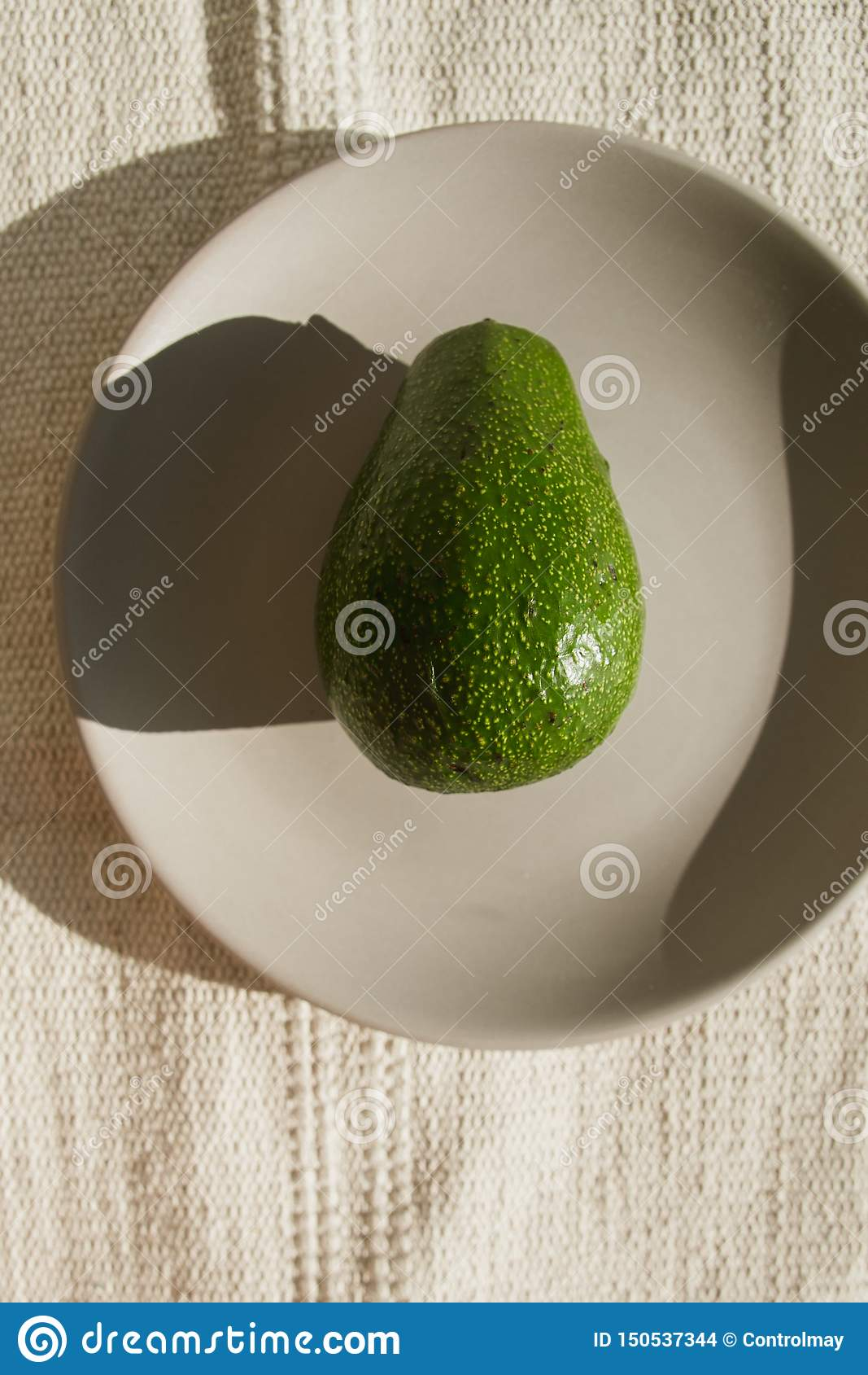 Green whole ripe avocado lies on a gray ceramic plate in the sun. One avocado is on a beige natural carpet in a hard light