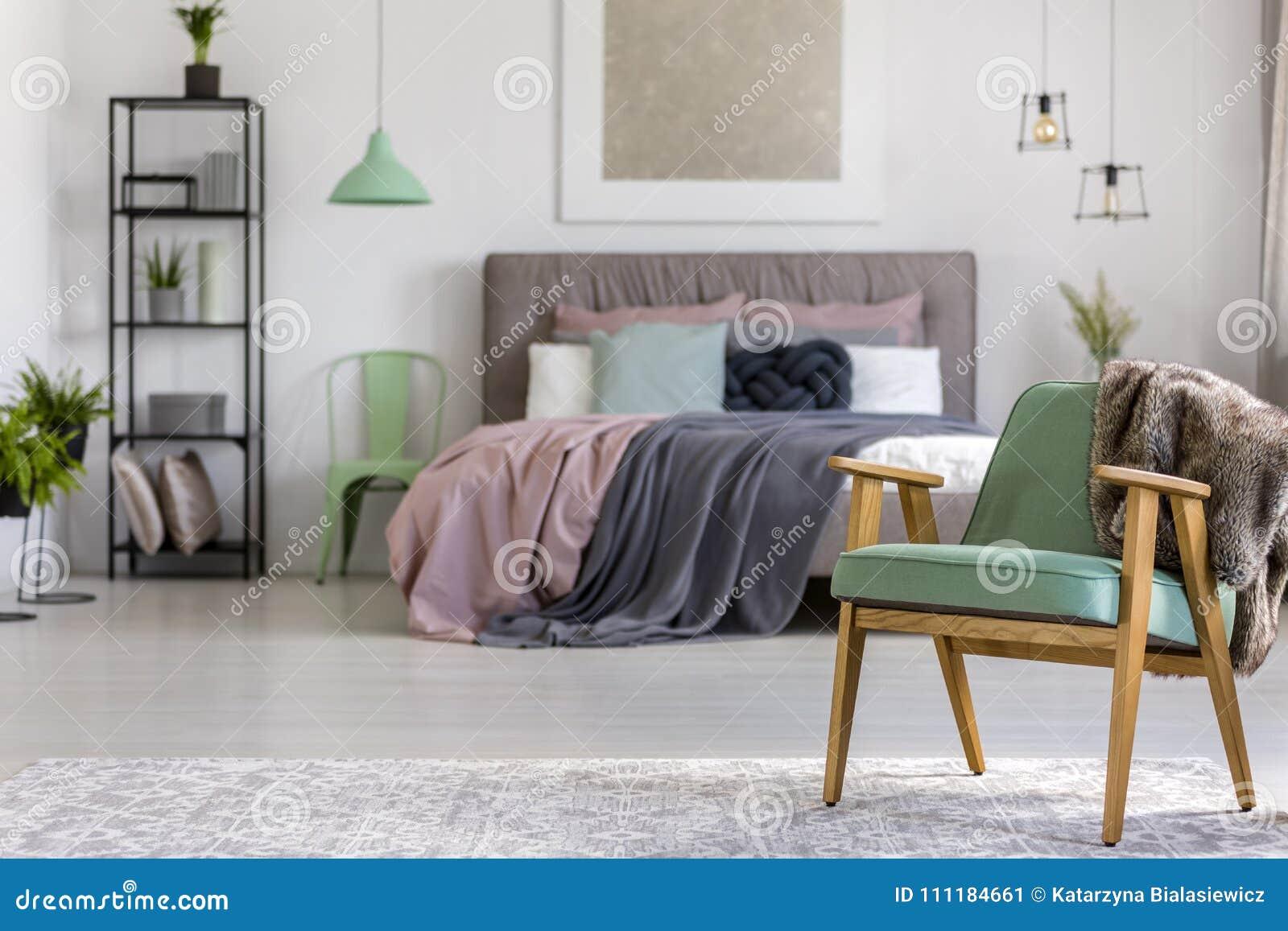 green wooden armchair bedroom green wooden armchair grey carpet bedroom interior lamps painting above bed