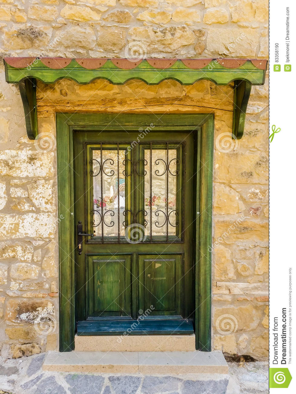 Green wooden door with wrought iron of a stone building for Door of stone