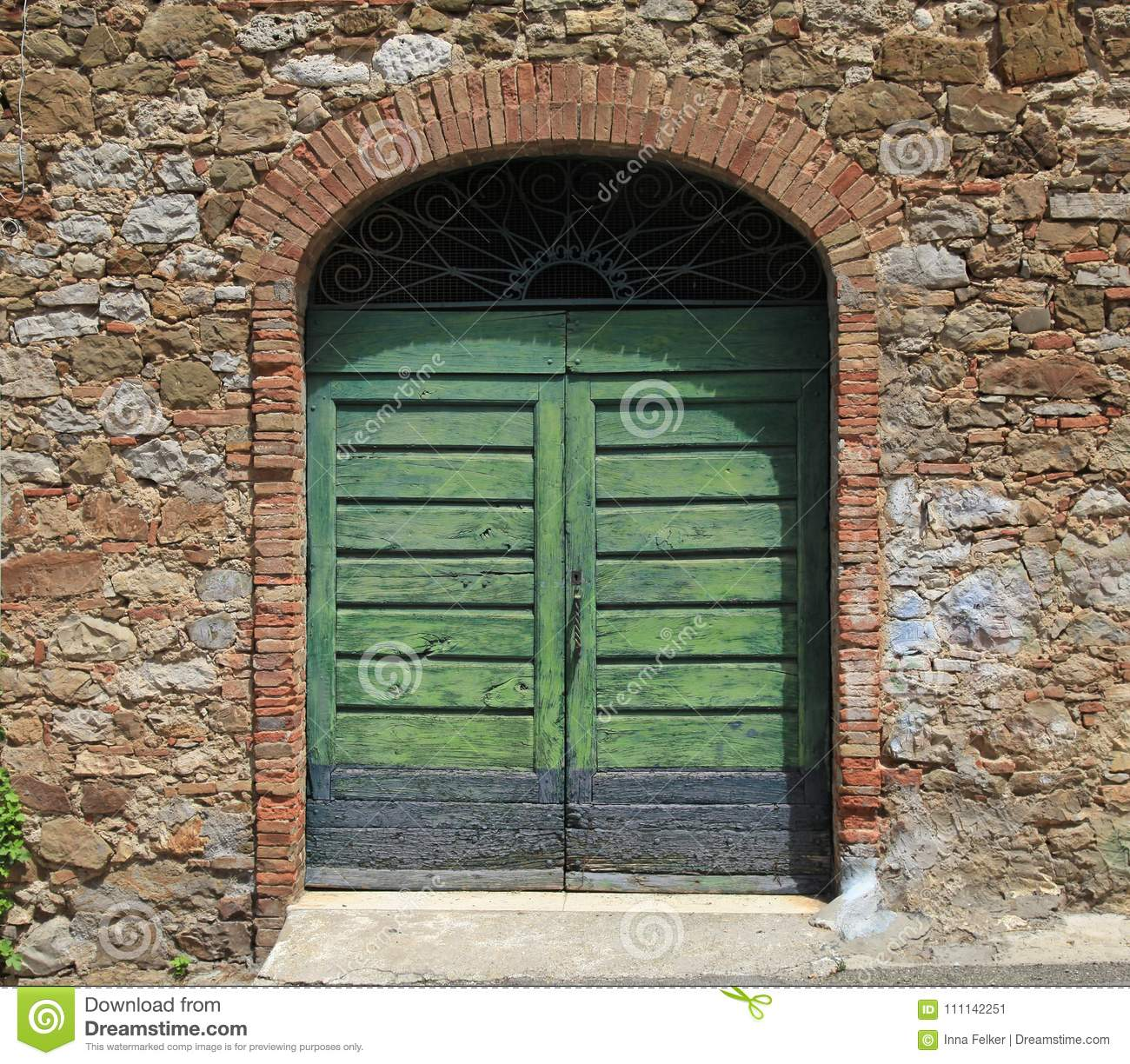 Green wooden gate in old stone Italian house