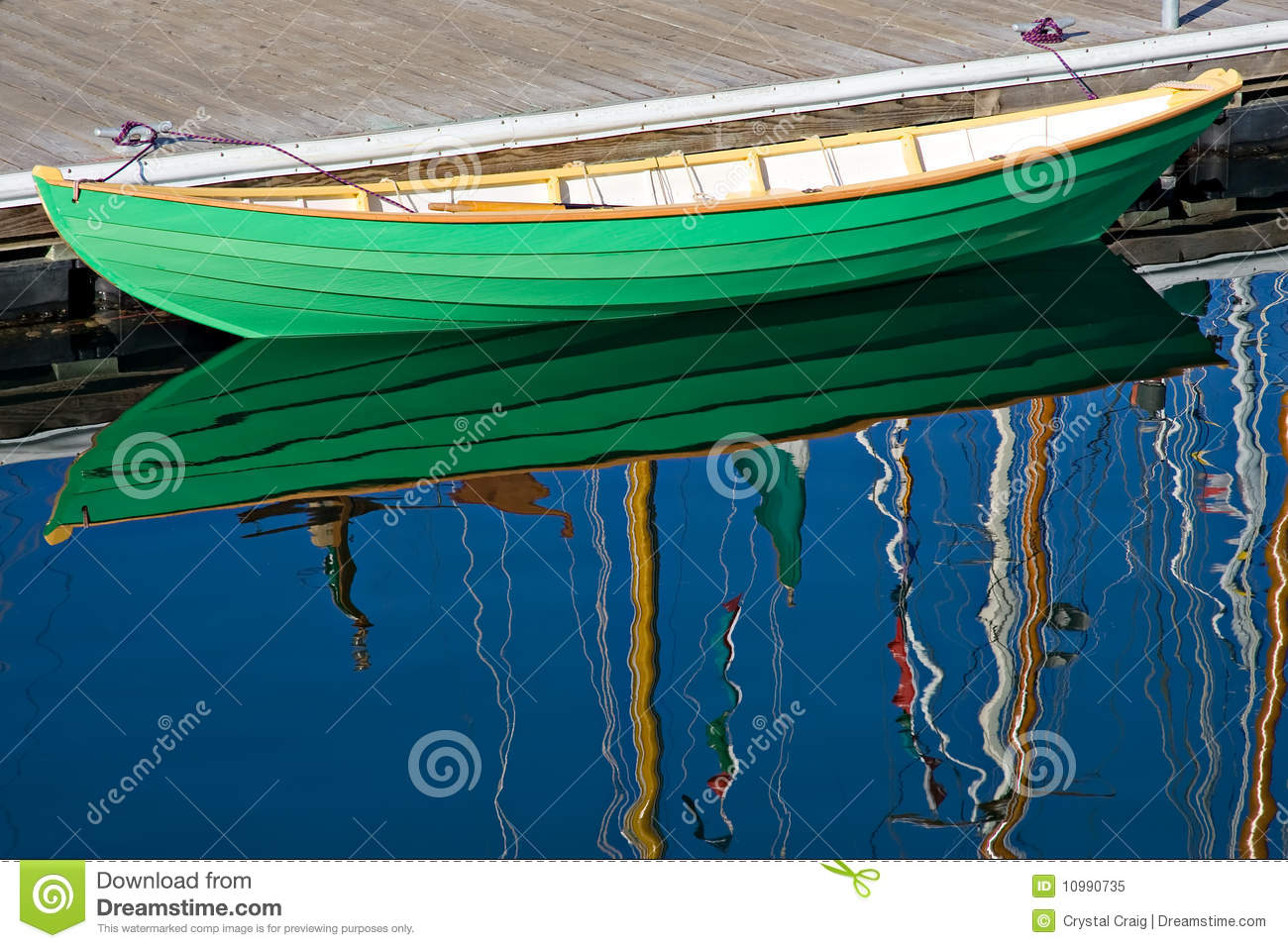 Beautifully crafted wooden row boat resting dockside in brightly ...