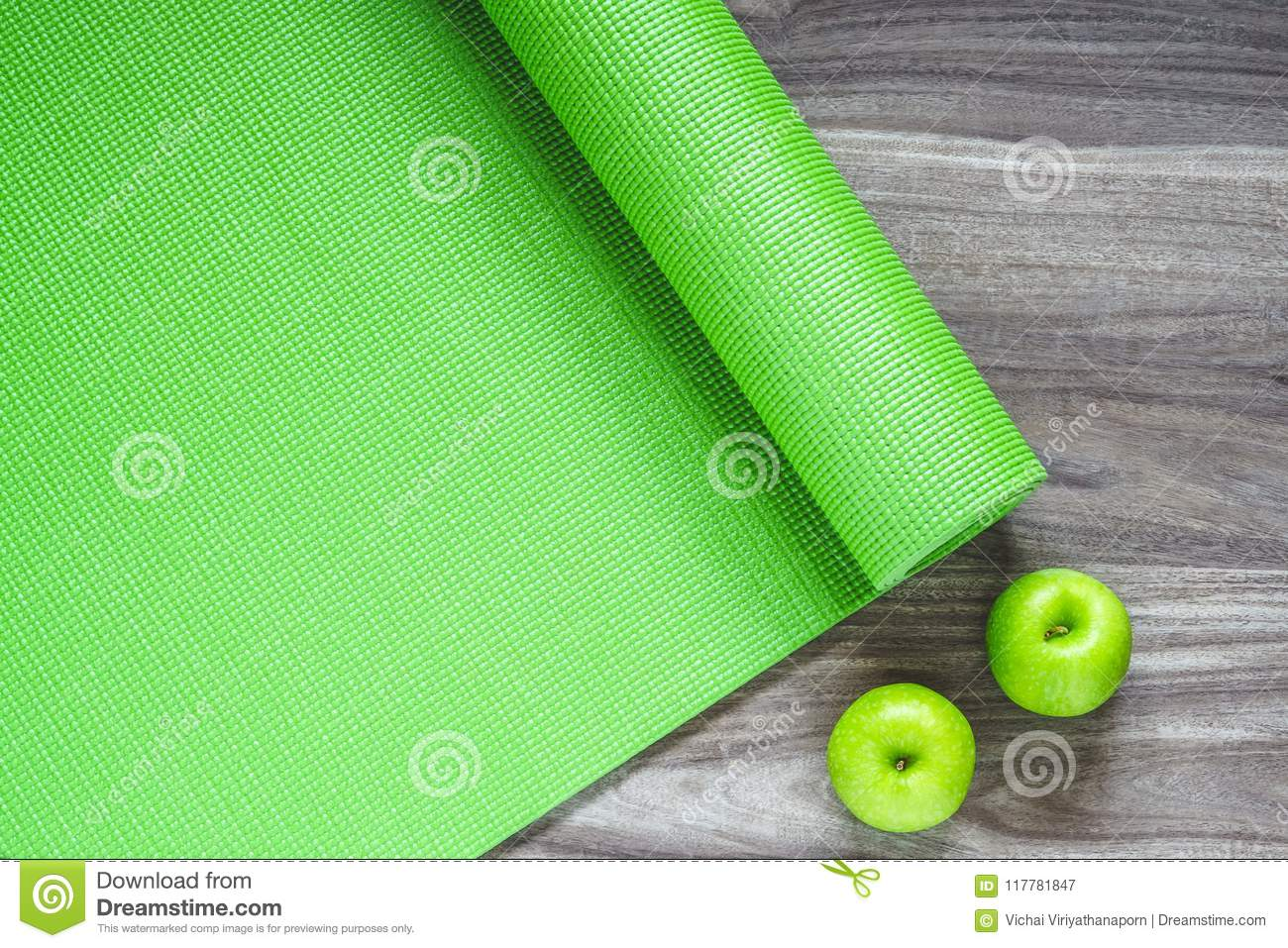 d777fa45a7e8f Green yoga mat on a wooden background with green apples, Top View with copy  space. Active healthy lifestyle background concept.