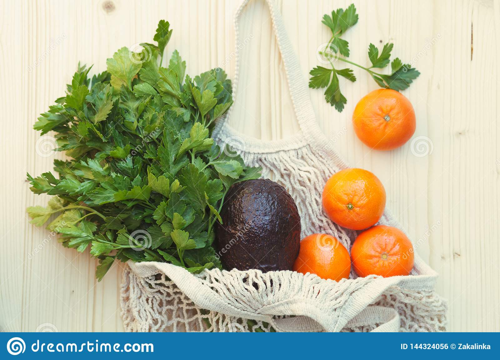 white eco-friendly reusable string bag with fresh fruits, herbs and vegetables, avocado, parsley, oranges on wooden background