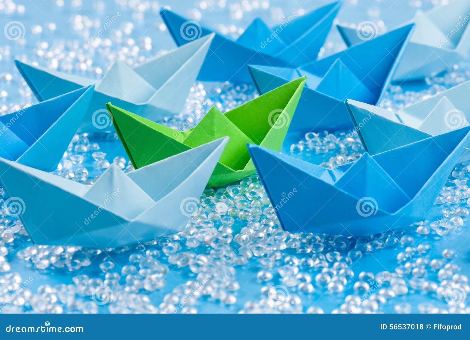 Greenpeace: Vloot van blauwe Origamidocument schepen op blauw water zoals achtergrond die groene omringen