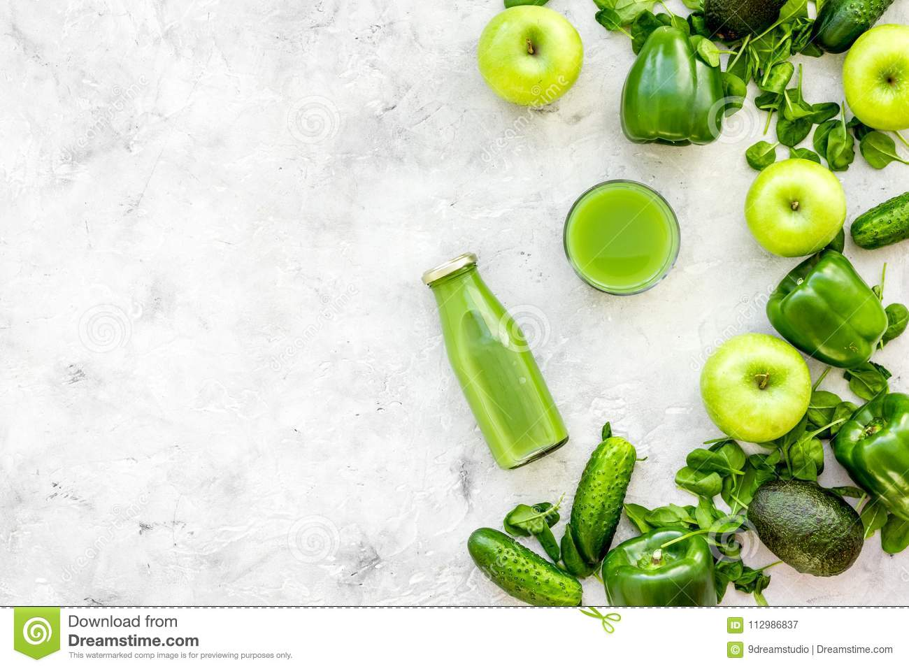 Greeny vegetable smoothie in bottle with cucumber, pepper, apple, celeriac on stone background top view mock up