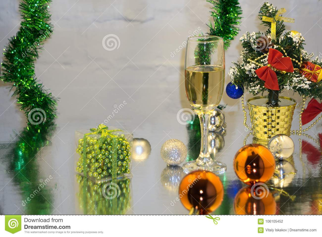 Greeting card made of christmas and yew year decoration balls, tinsel, candle and two glasses of champagne with reflection, copy s