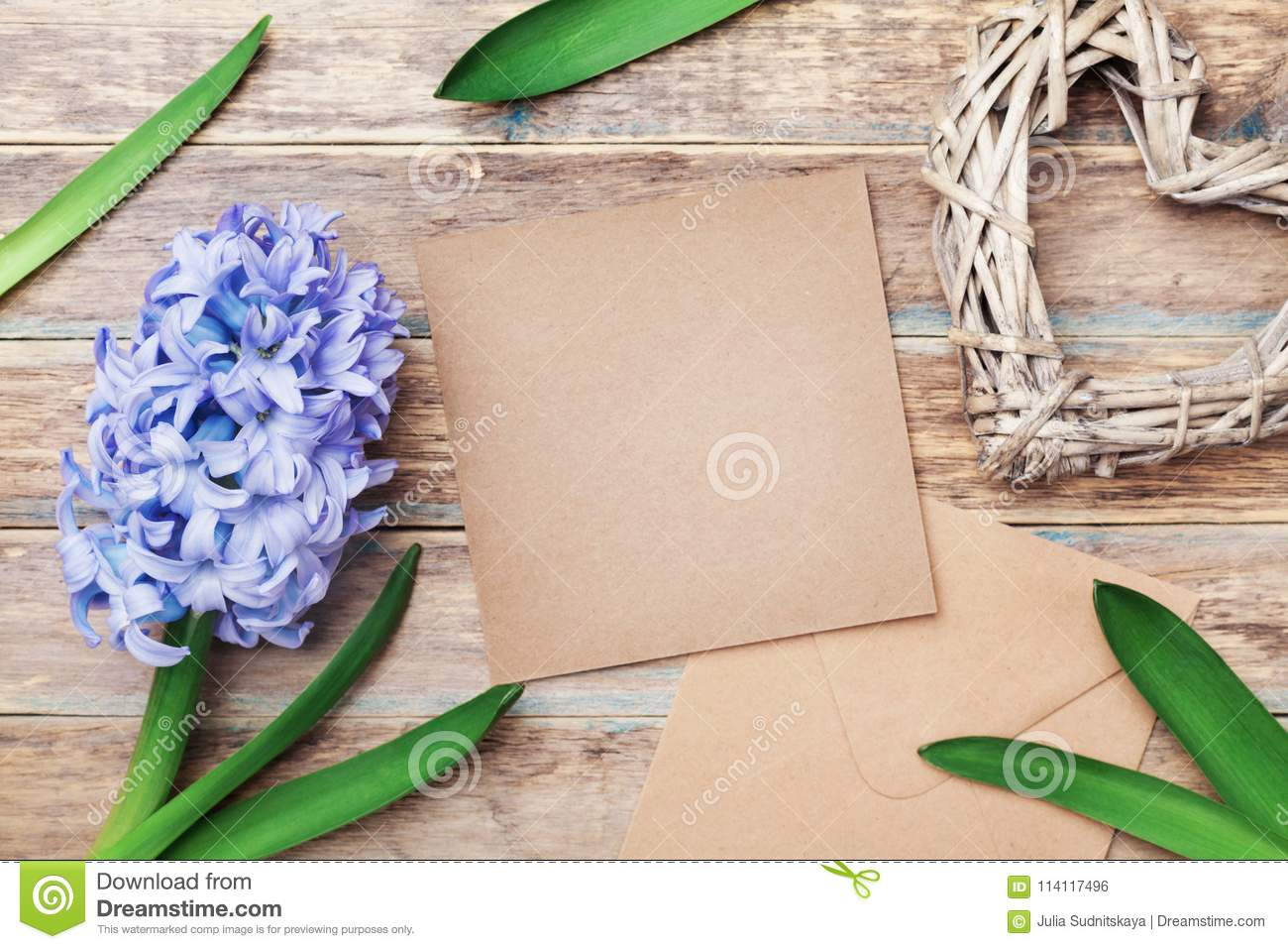 Greeting card on Mothers Day with kraft envelope decorated hyacinth flowers and heart on rustic background. Top view.