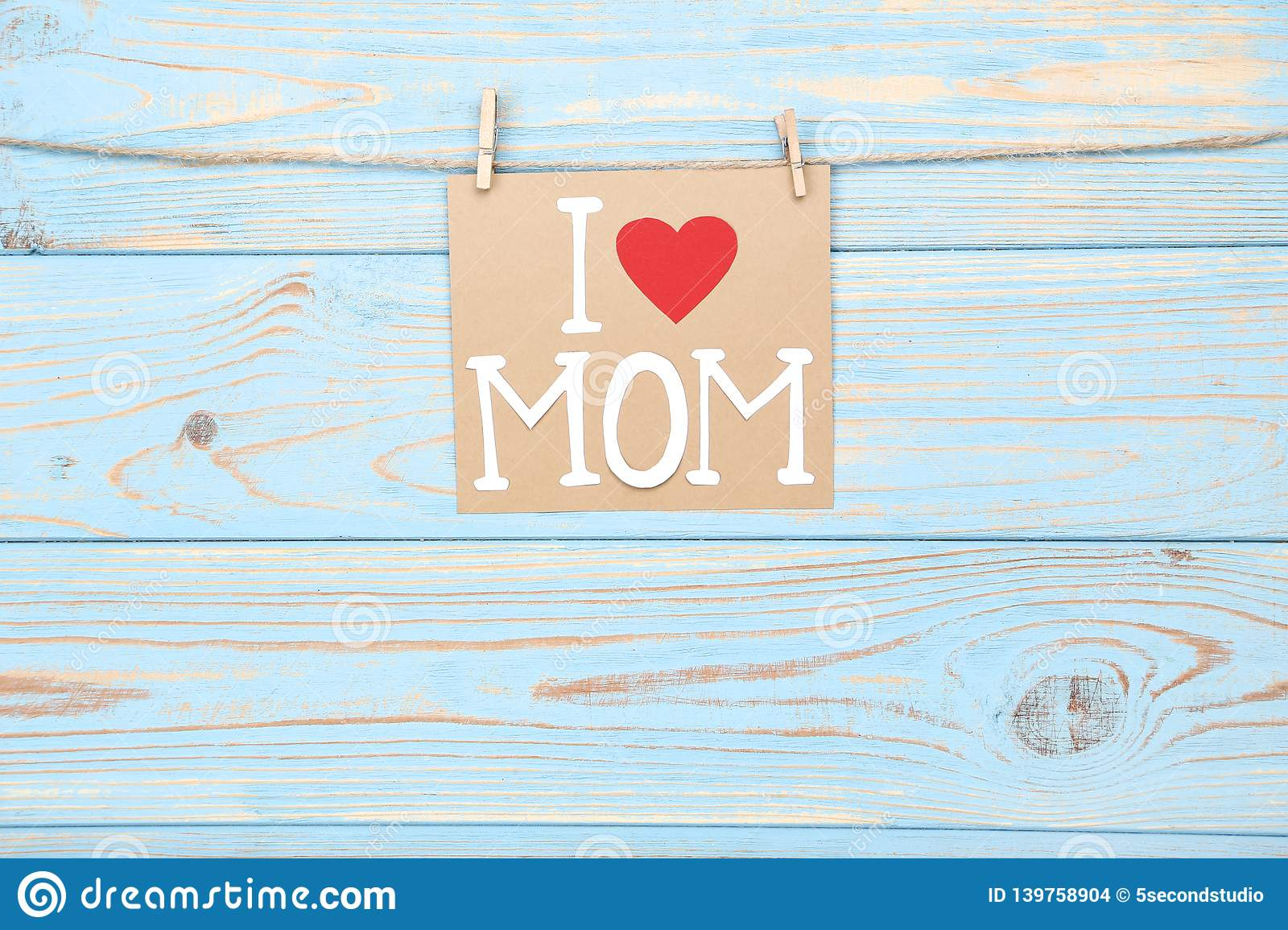 Greeting card with text I Love Mom hanging on wooden background stock images