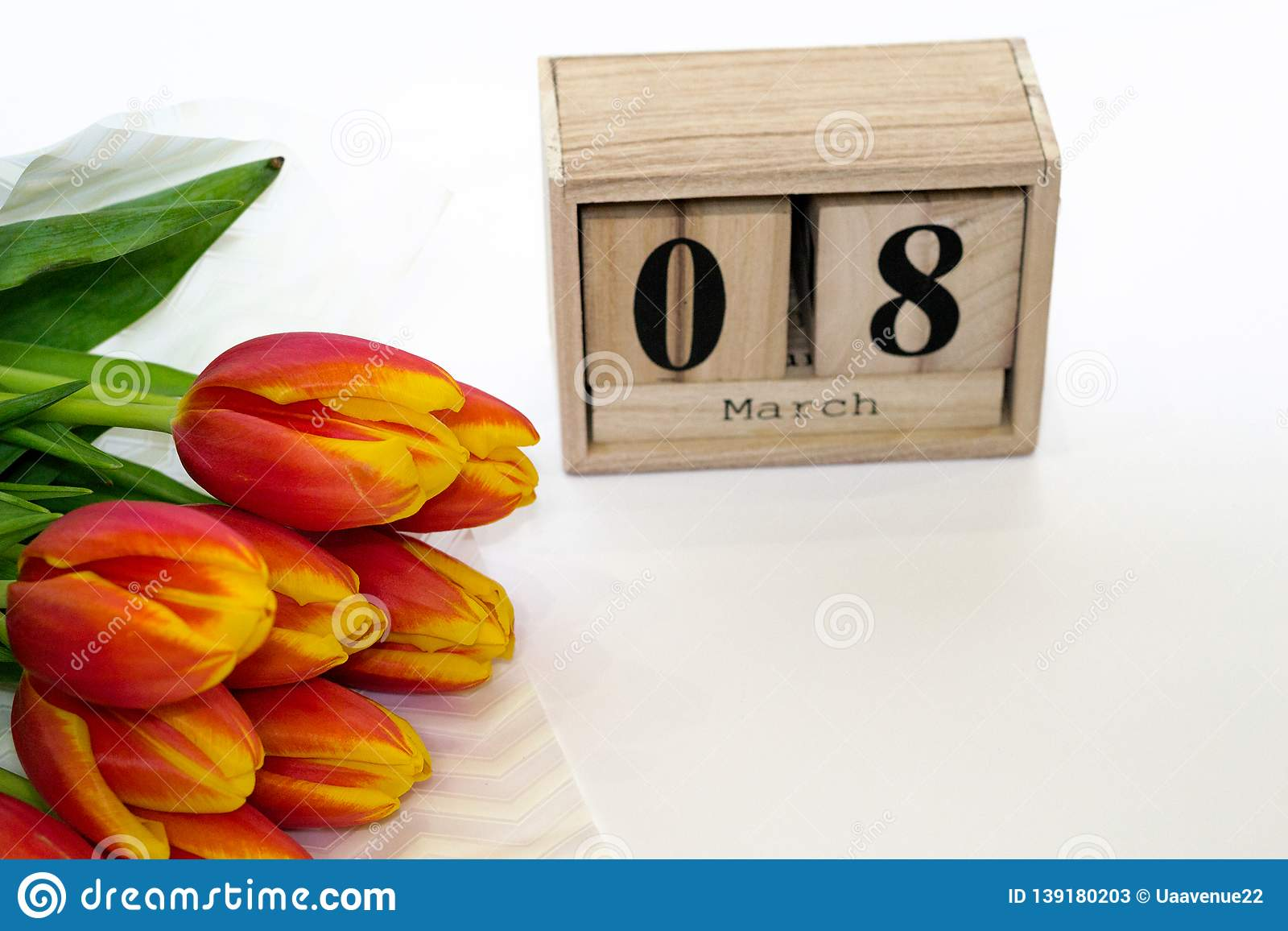 Greeting card for 8th March. International Women`s day background with bouquet of red tulips and wooden calendar of 8 march. Copy
