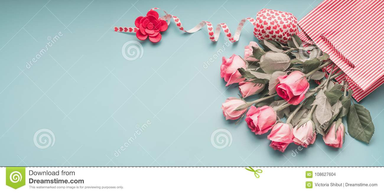 Greeting pink pale roses bunch in shopping bag with ribbon on turquoise blue background, top view