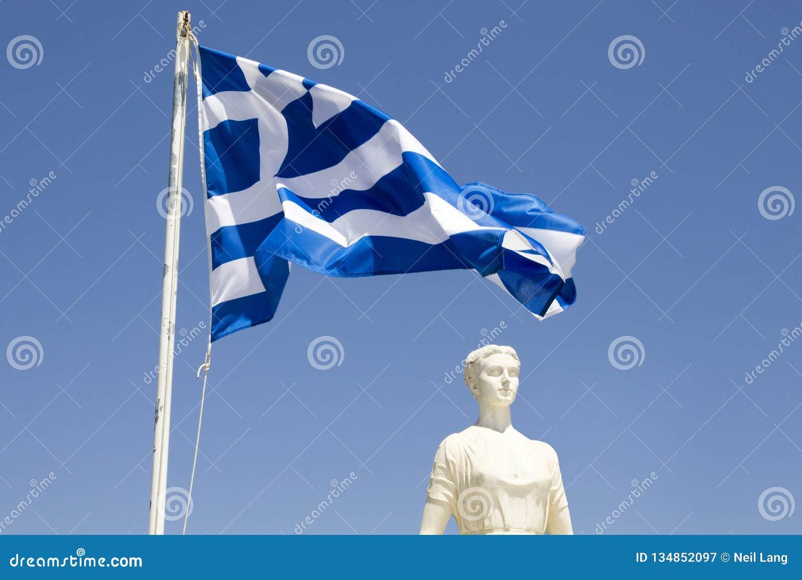 Grek flaga z białą marmurową statuą w Skiathos schronieniu, Skiathos miasteczko, Grecja, Sierpień 18,