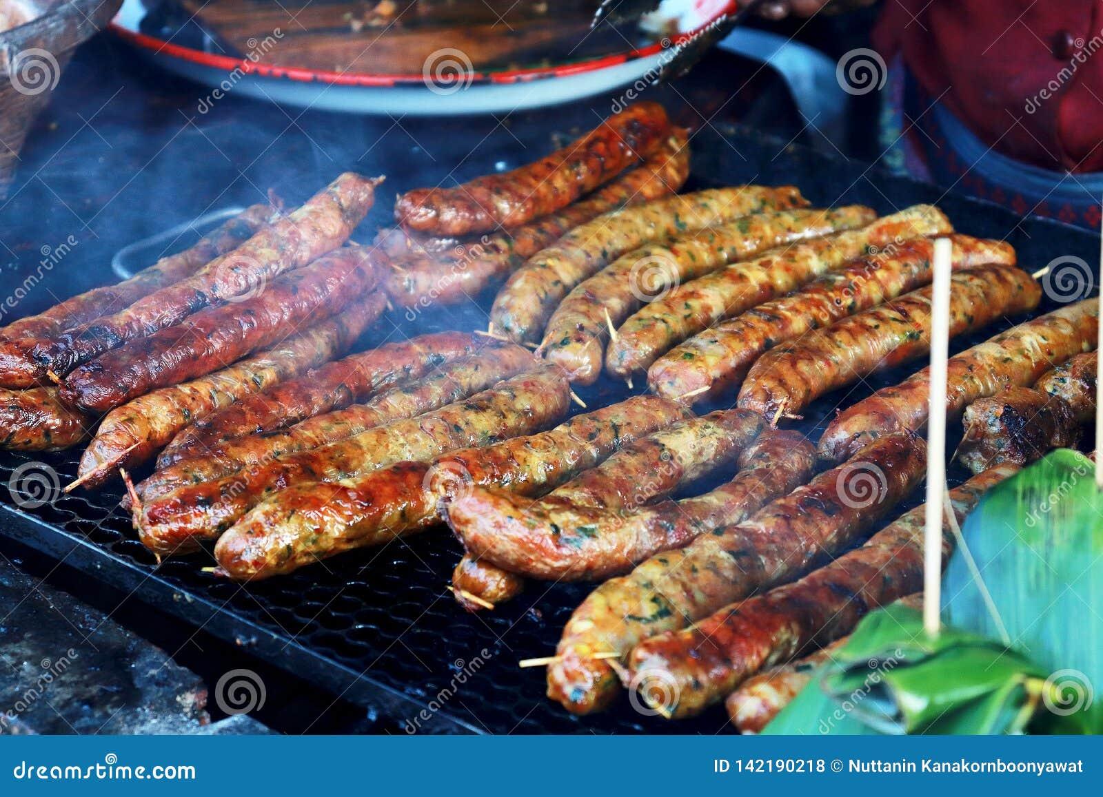Grelhando salsichas tailandesas na grade do assado BBQ no jardim Salsichas bávaras