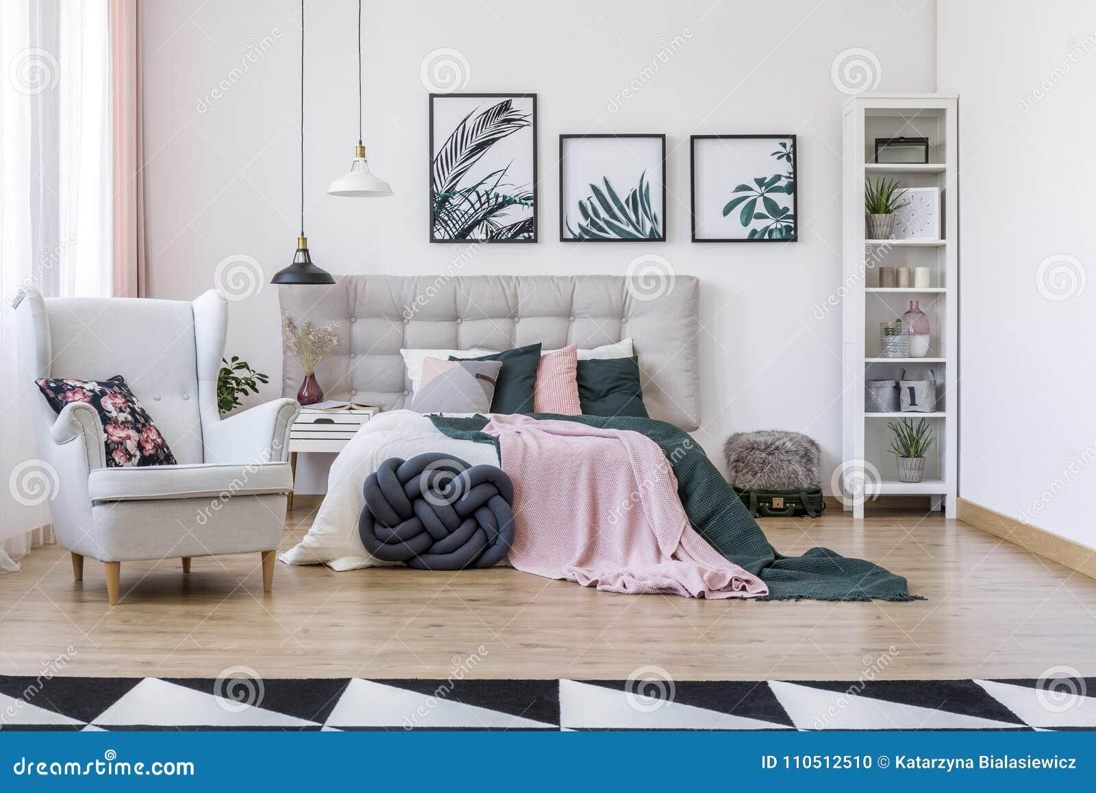 grey armchair bedroom interior knot pillow near bed pink green bedding near grey armchair bedroom interior
