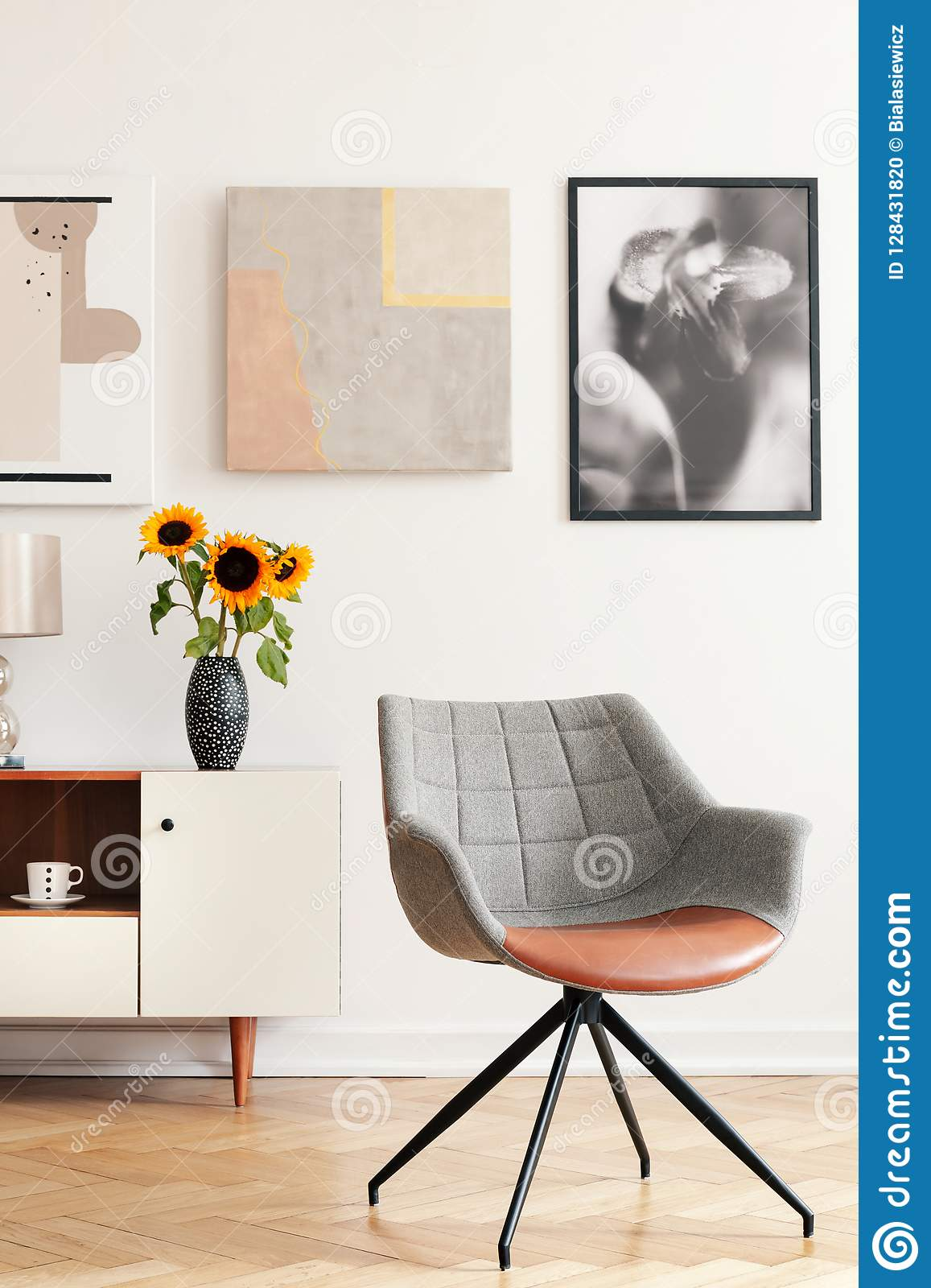 Grey armchair and sunflowers on cabinet in white living room interior with posters
