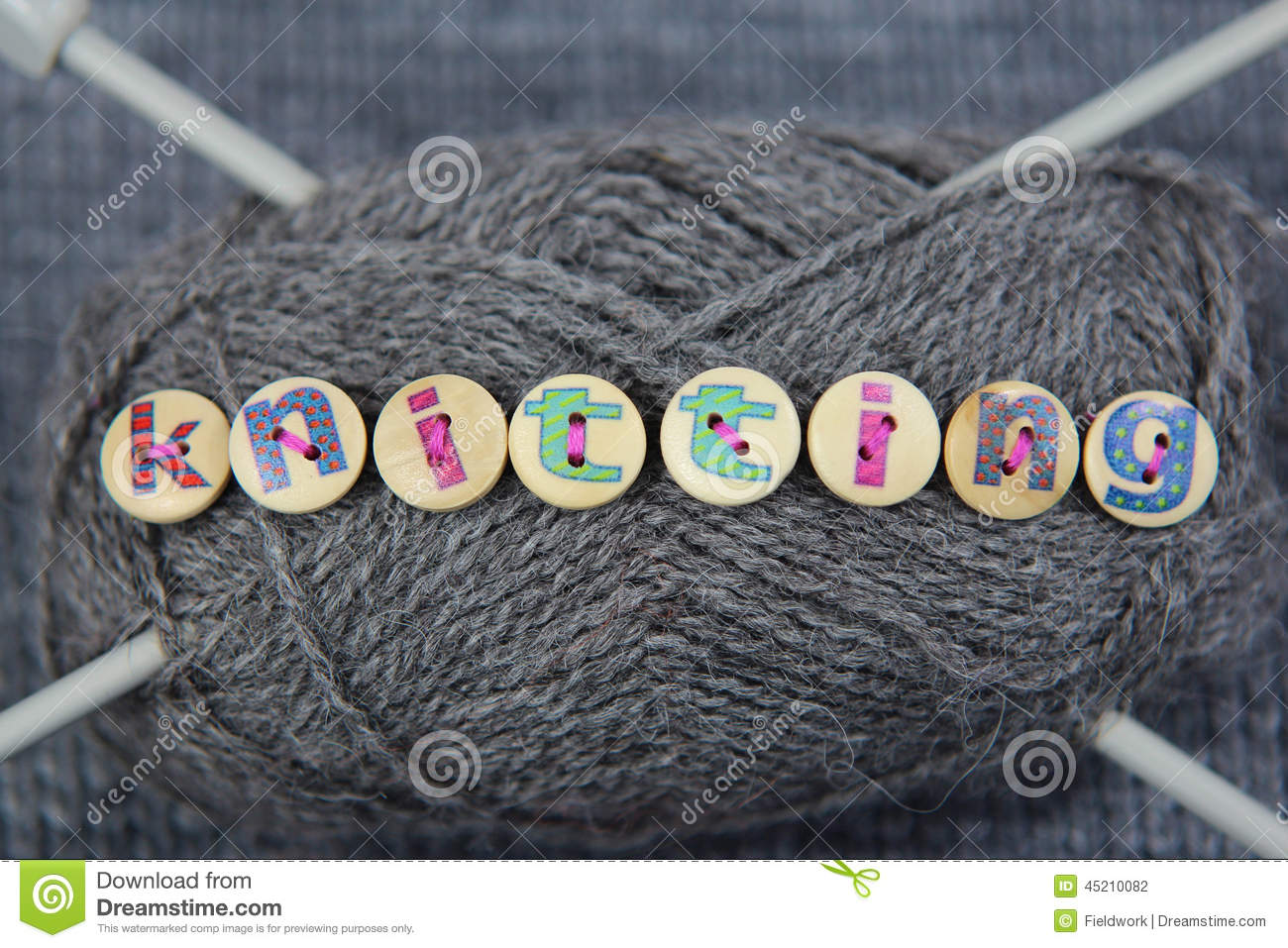 grey ball of wool with the word knitting spelled in