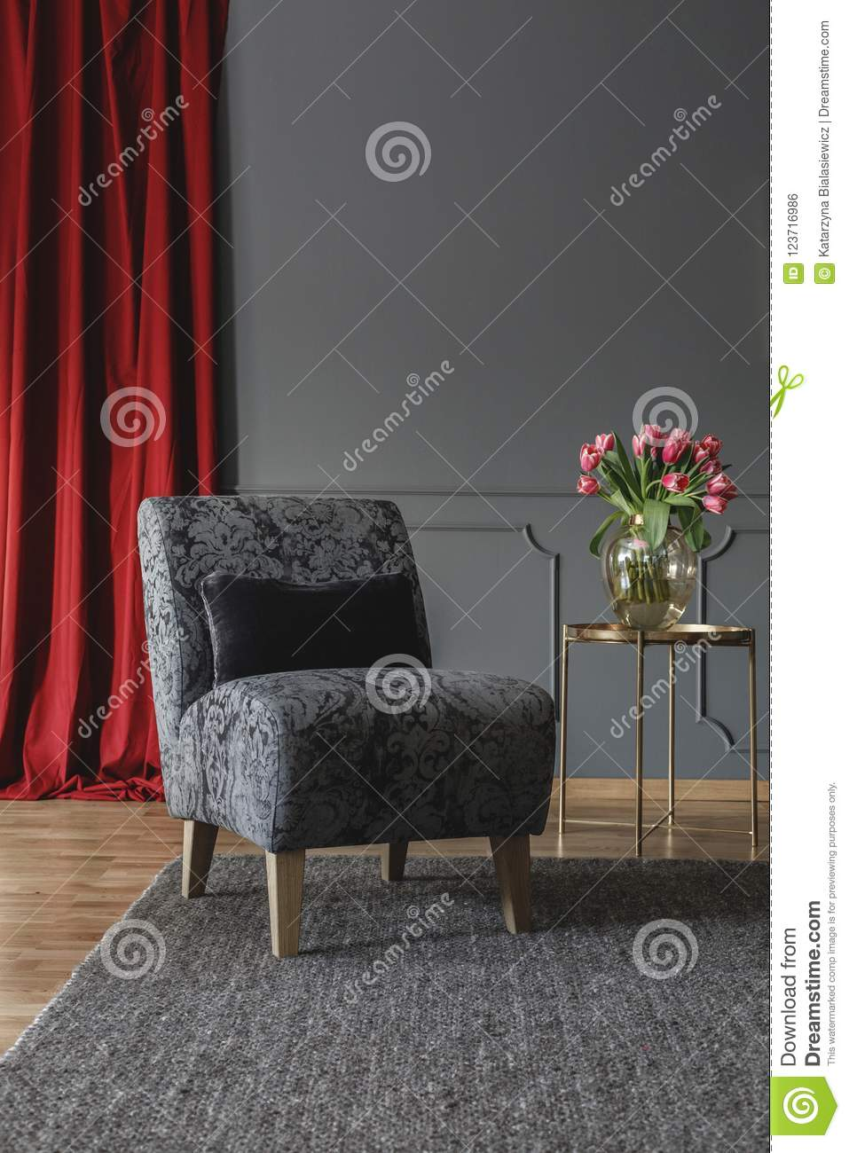 Grey Floral Chair With Black Cushion Standing On Dark Carpet In