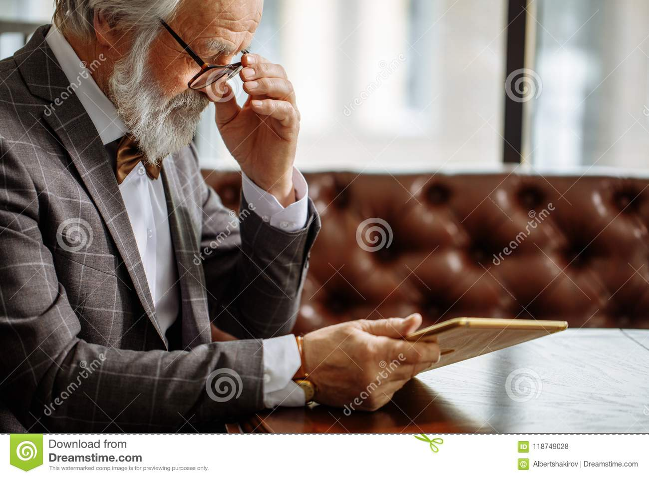 Grey Haired Man In Glasses Using IPad At Home Stock Photo ...