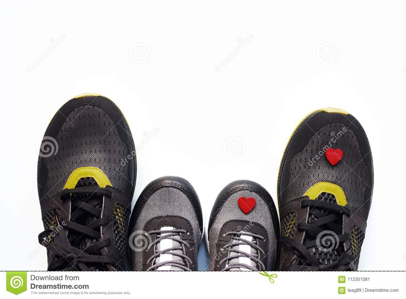 Grey kid sneakers with little red heart and pair of black adult sneakers