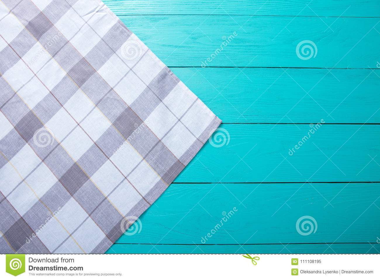 Grey plaid tablecloth on blue rustic wooden table, top view and copy space. Mock up and wood background.
