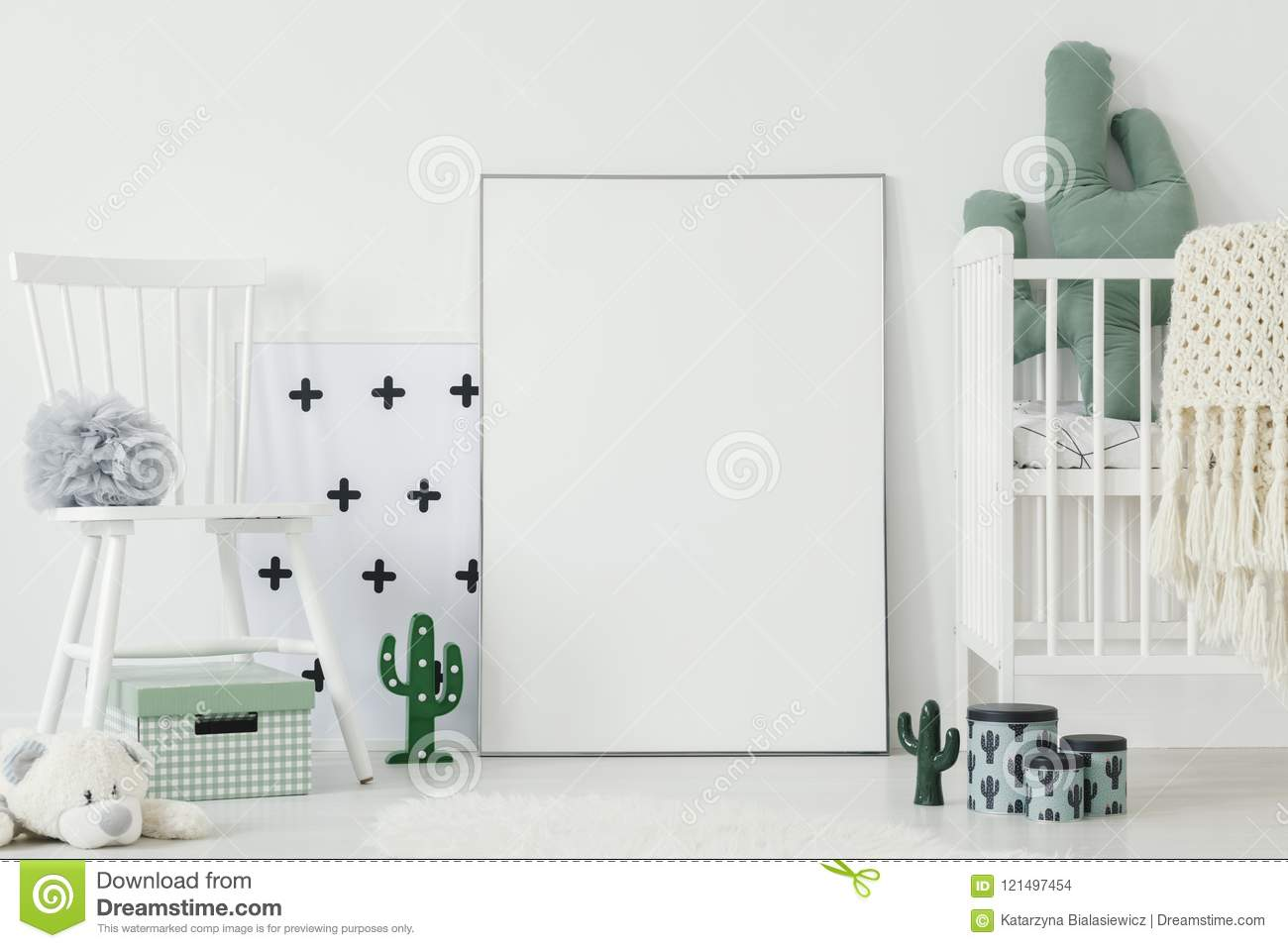 Grey pompom placed on white chair standing in bright baby bedroom interior with cactus shaped decor and empty poster on the floor
