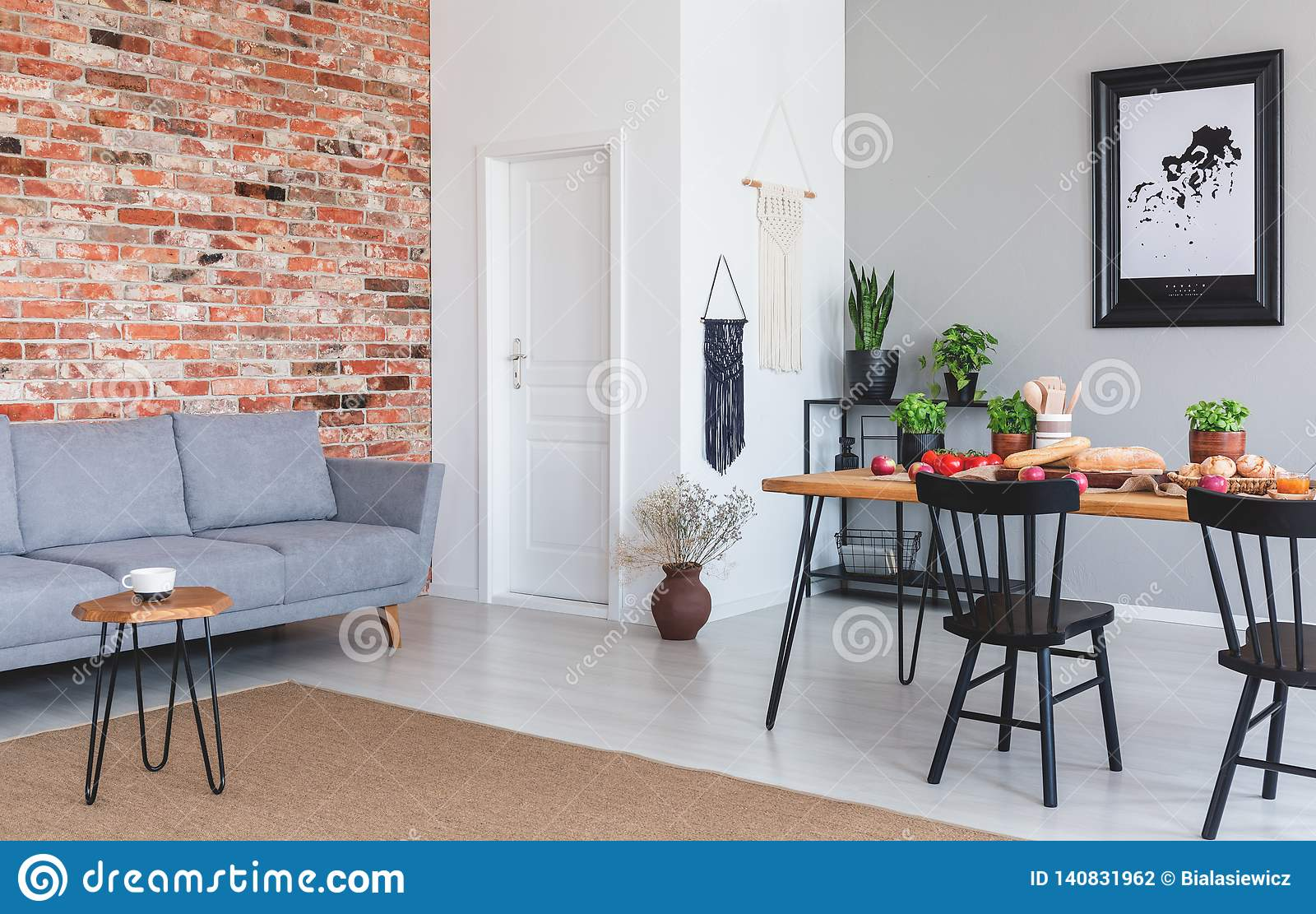 Grey Sofa Against Red Brick Wall In Flat Interior With