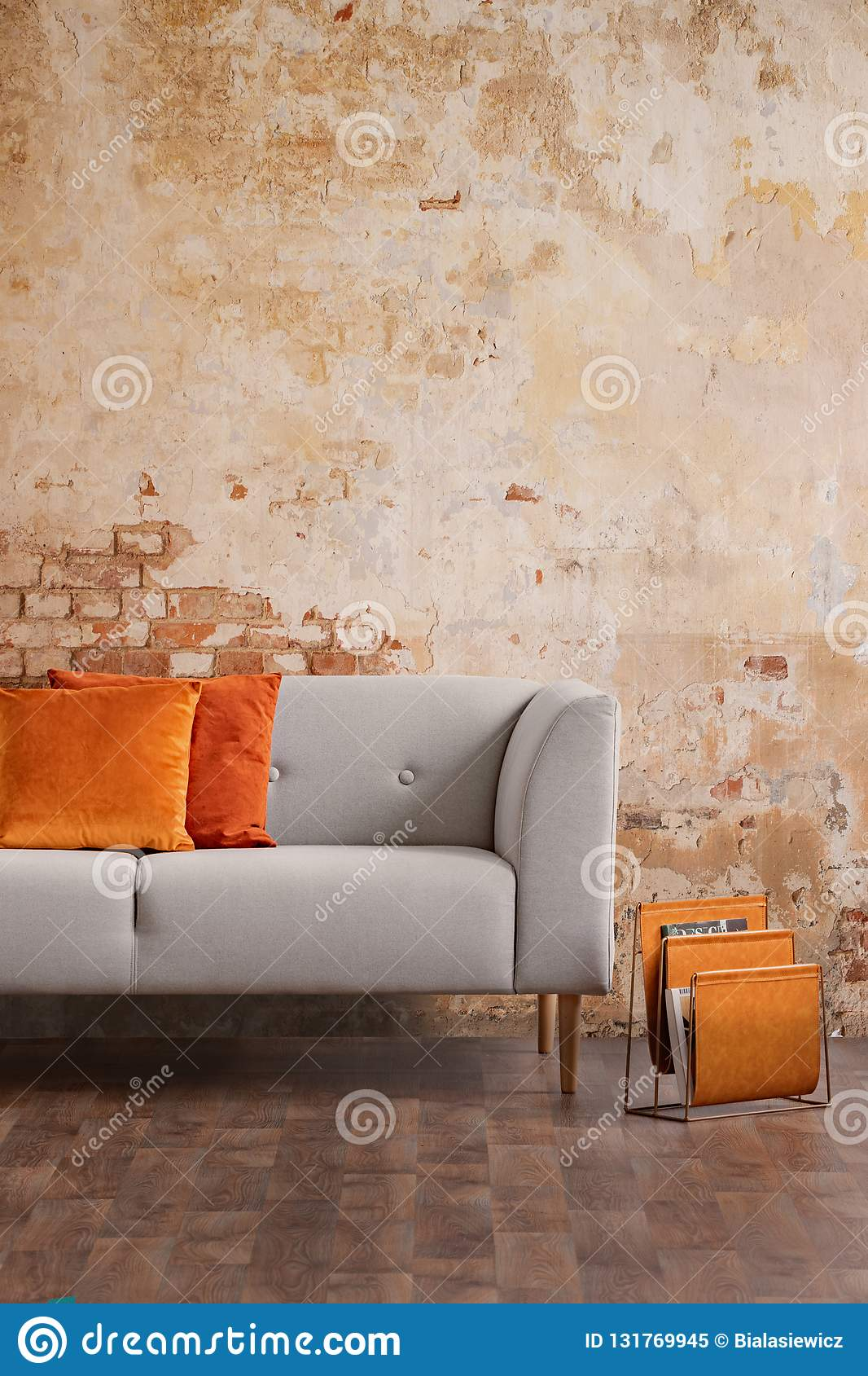 Grey sofa against red brick wall in modern living room interior. Real photo