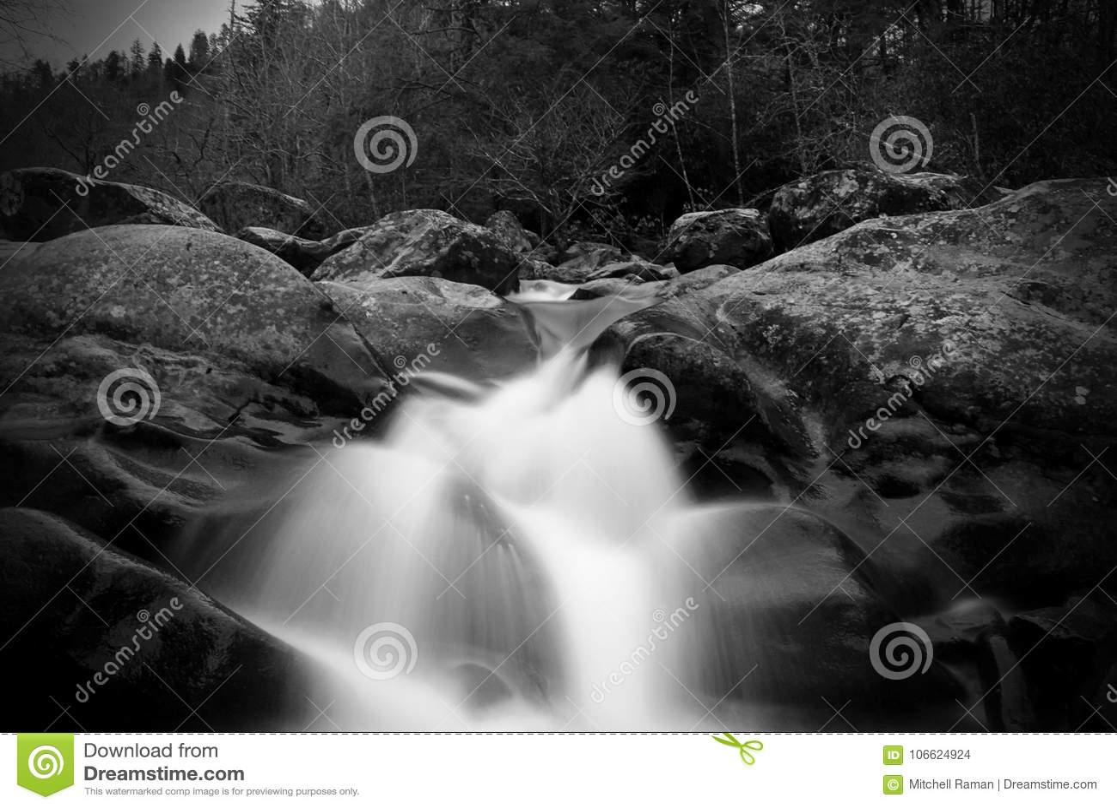 Greyscale θολωμένη κίνηση και αργή φωτογραφία Waterscape παραθυρόφυλλων μιας πτώσης νερού πέρα από μεγάλες πέτρες