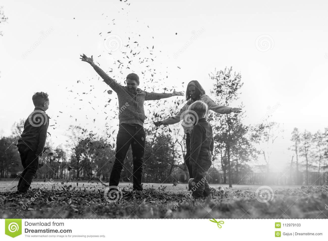 Greyscale image of young family playing with autumn leaves stand