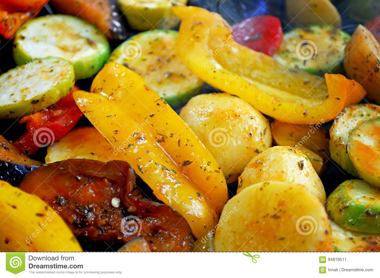 On the grid grill are fried vegetables. Potatoes, tomatoes, peppers, eggplants, cucumbers, zucchini, carrots and seasonings with o