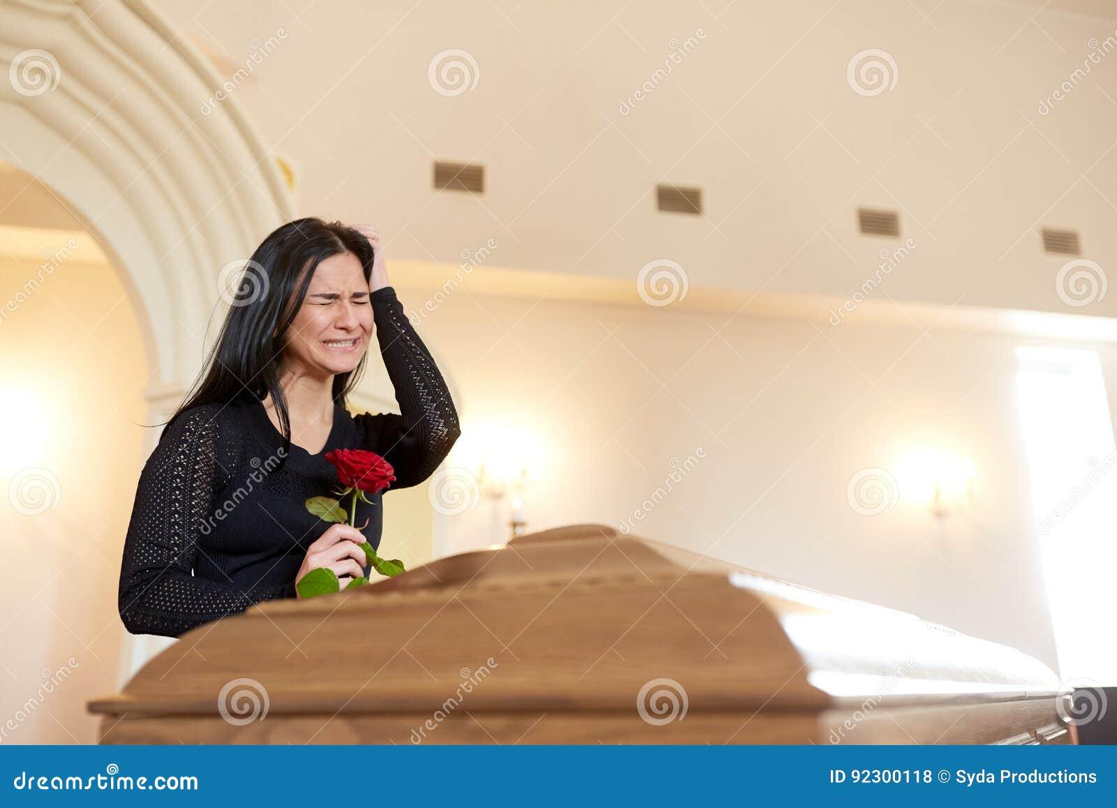 Gridare donna con la rosa rossa e la bara al funerale