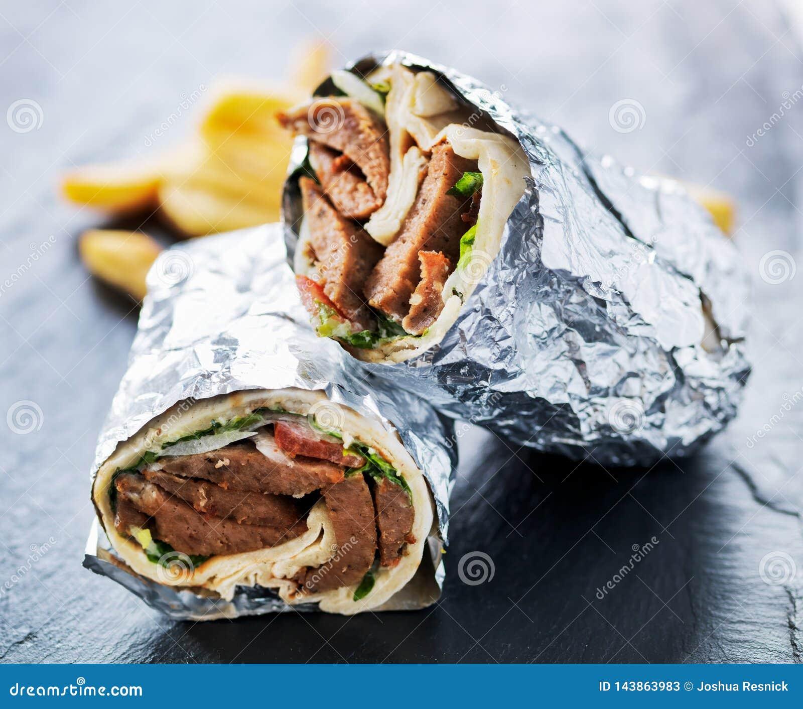 Griekse die gyroscoop in folie wordt verpakt in de helft wordt en met gebraden gerechten wordt gediend gesneden die
