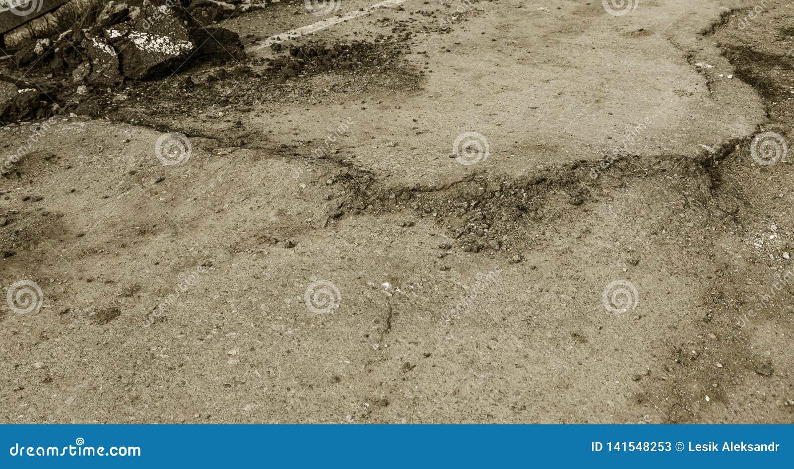 Grietas grandes, microprocesadores, placas El asfalto roto desplazó derrumbamiento después de un terremoto Grietas profundas peli