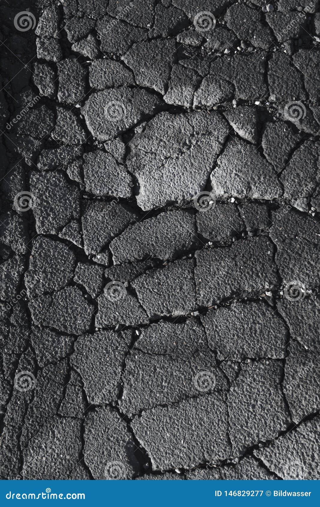 Grietas y grietas en un camino de la calle del asfalto