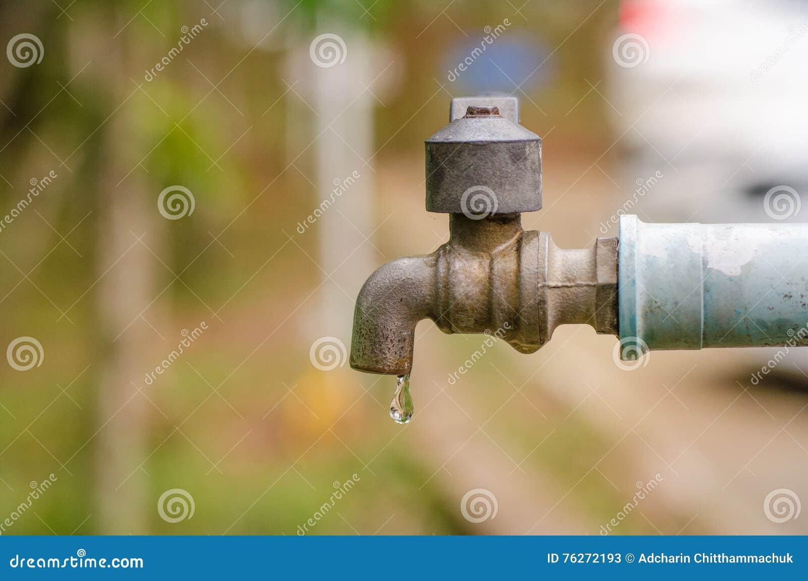 Grifo viejo defectuoso y tubo del PVC Despilfarro de la causa del agua y del Dr.