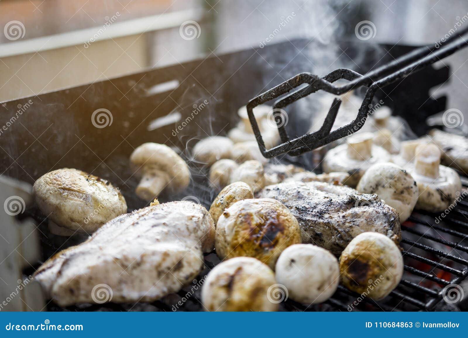 Griglia del BBQ con molti funghi e petto di pollo saporito