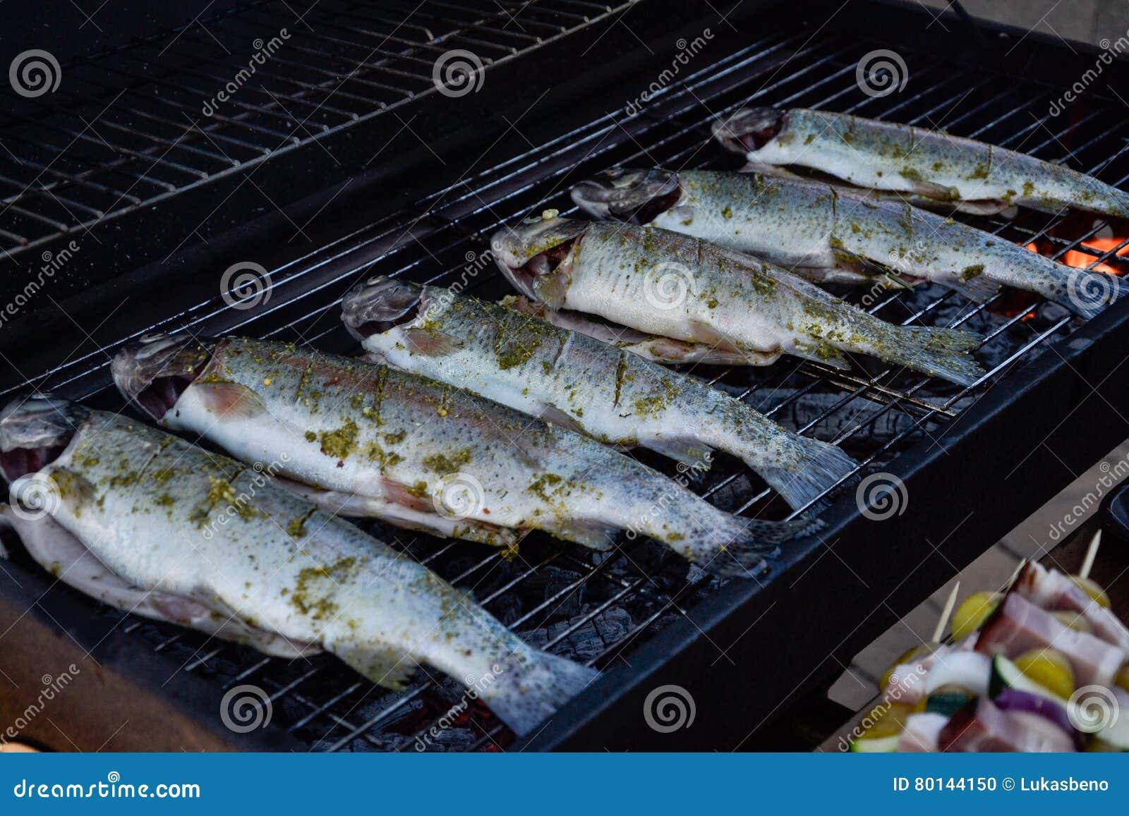 Grigliare i pesci interi sulla griglia in giardino le - Nascondere griglia giardino ...