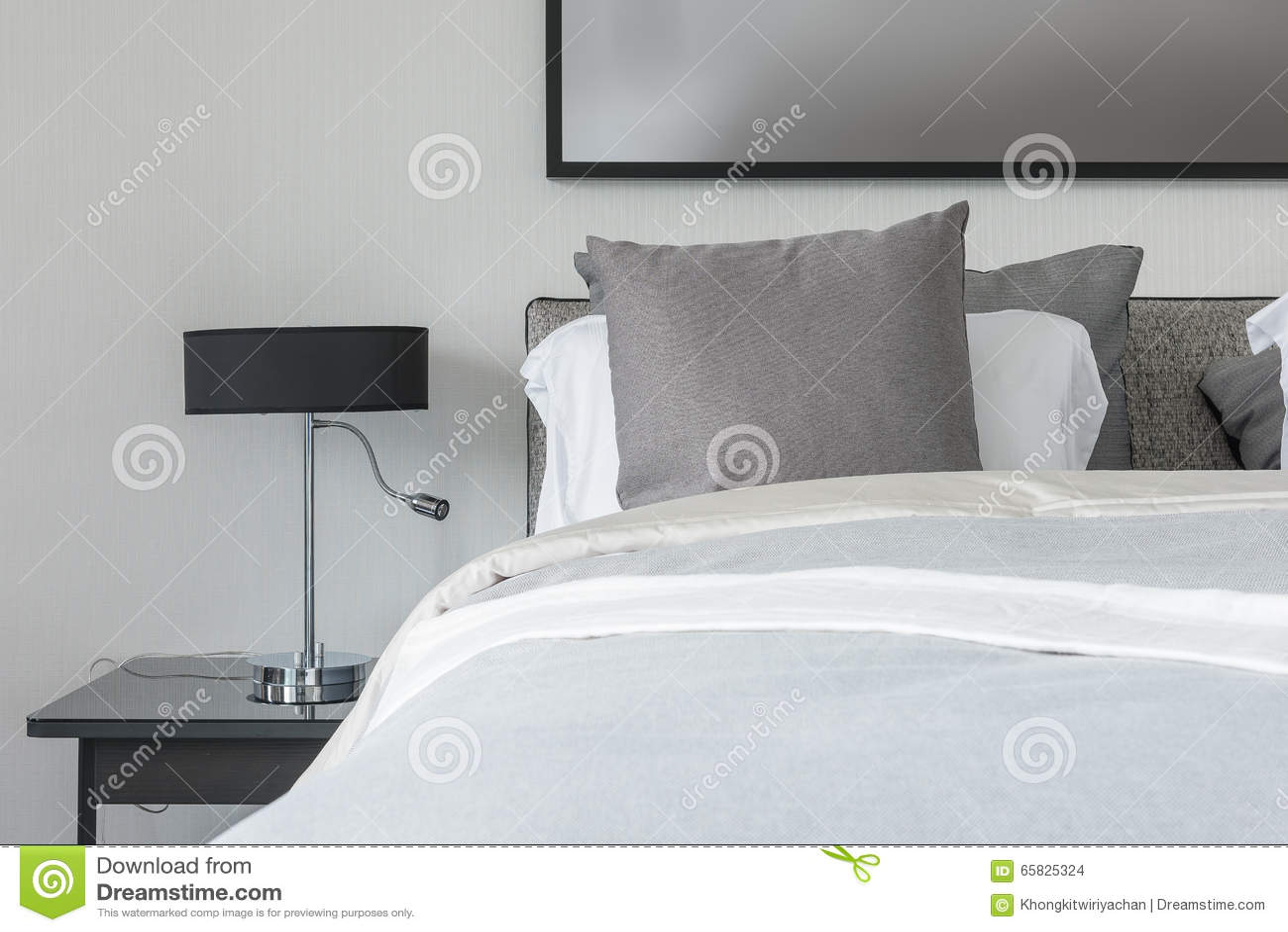 Grijze Slaapkamer Lamp : Grijs hoofdkussen op wit bed in moderne slaapkamer met zwarte