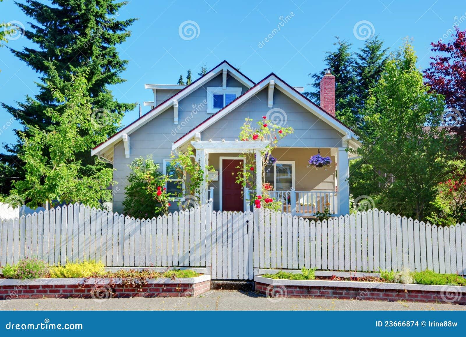 Leuke Ventilator Huis : Grijs klein leuk huis met witte omheining en poorten. stock foto