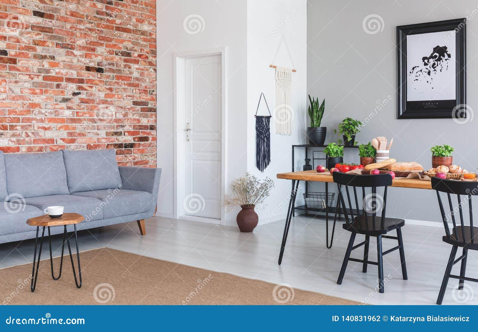 Grijze bank tegen rode bakstenen muur als vlak binnenlands met affiche en zwarte voorzitter bij eettafel Echte foto