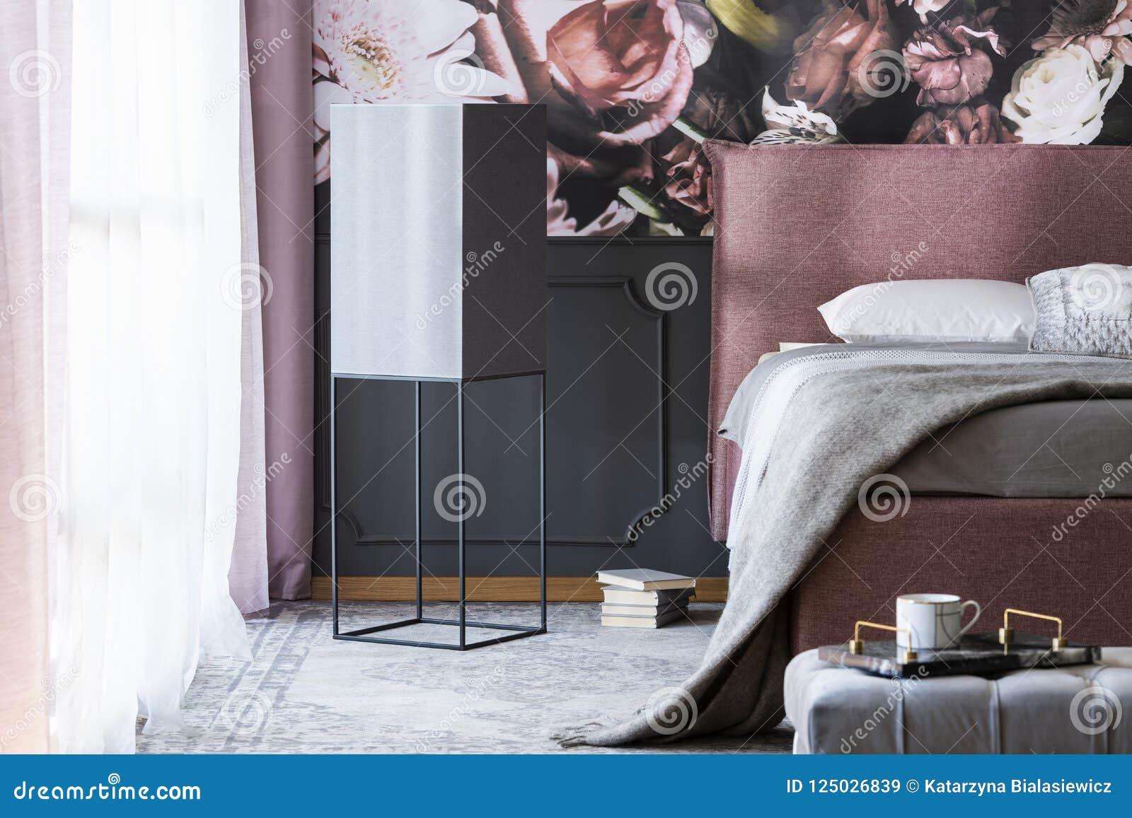 Roze Grijze Slaapkamer : Grijze deken en hoofdkussens op roze bed in donkere slaapkamer