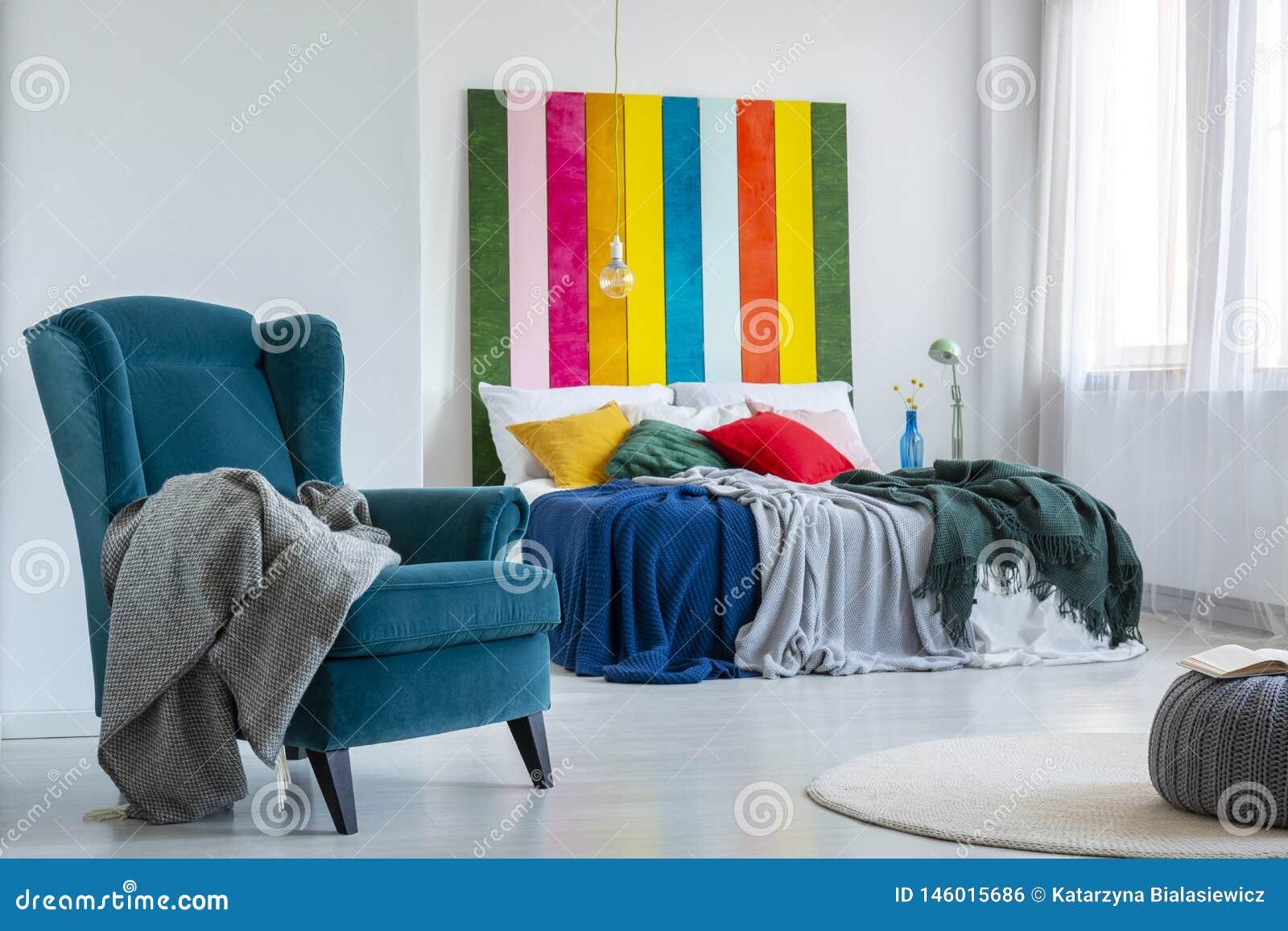 Grijze deken op een leunstoel op z n gemak, blauwe naast een kleurrijk bed met kussens in een helder slaapkamerbinnenland met het