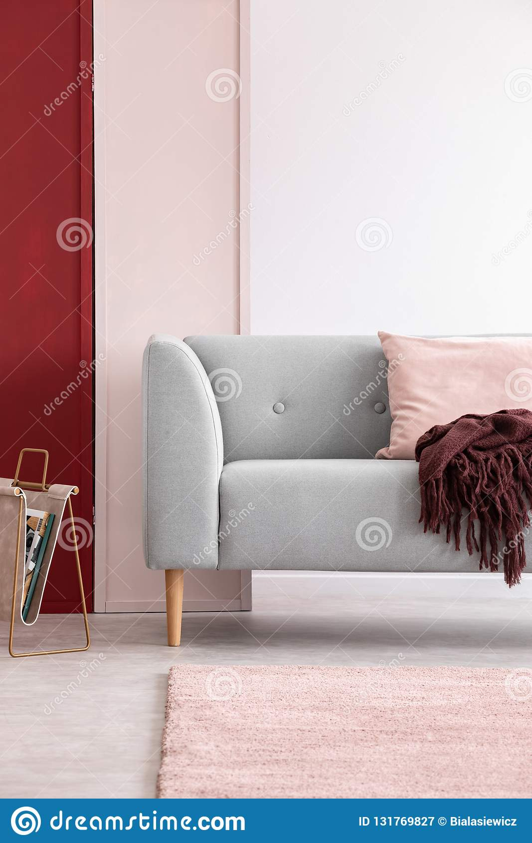 Grijze laag in helder woonkamerbinnenland met drie gekleurde muur, echte foto