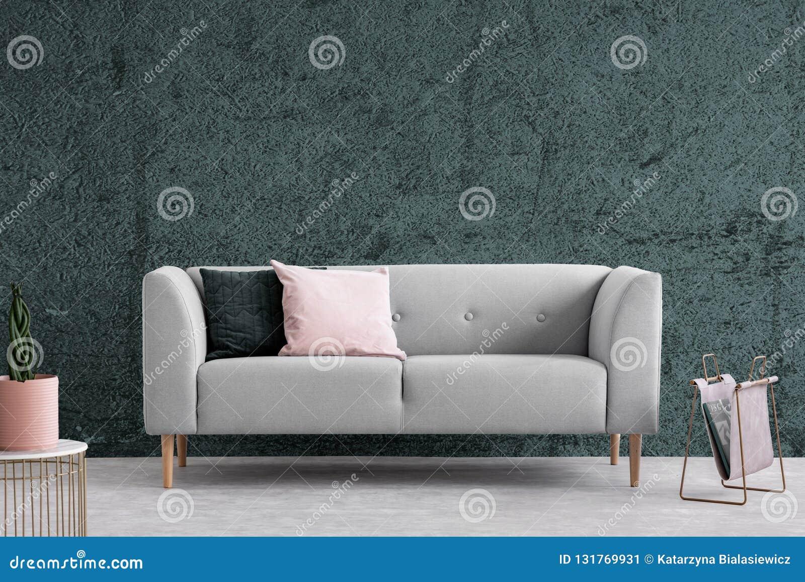 Grijze laag met kussens in donker flatbinnenland met geweven muur Echte foto