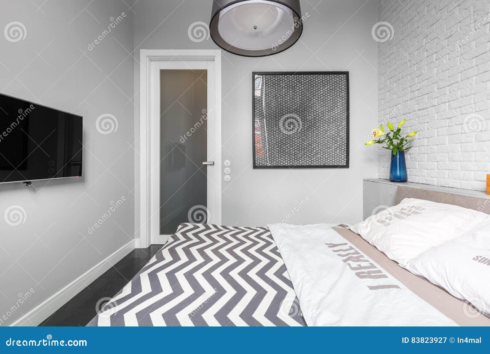 Grijze slaapkamer met TV stock afbeelding. Afbeelding bestaande uit ...
