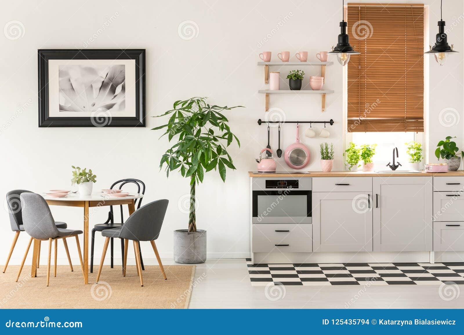 Grijze stoelen bij eettafel in helder binnenland met affiche en p