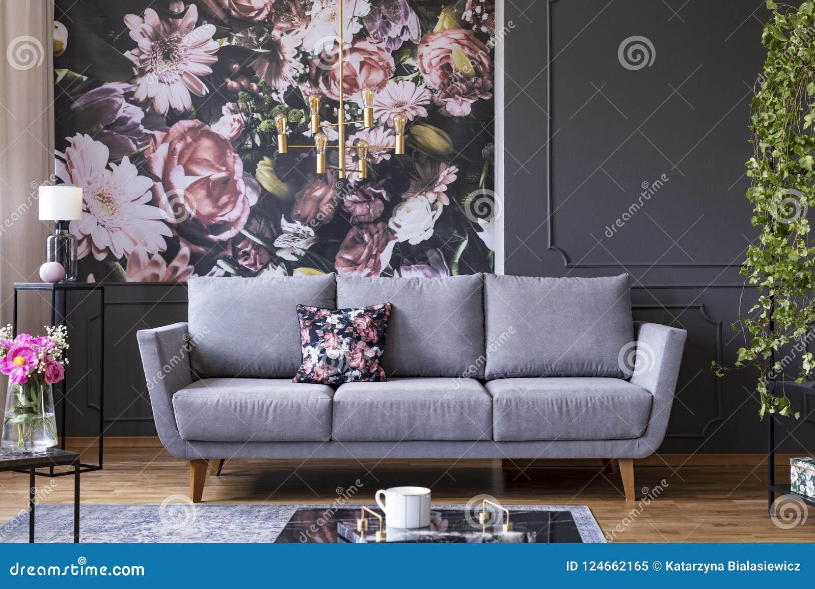 Grijze zitkamer met gevormd kussen in echte foto van het donkere leven