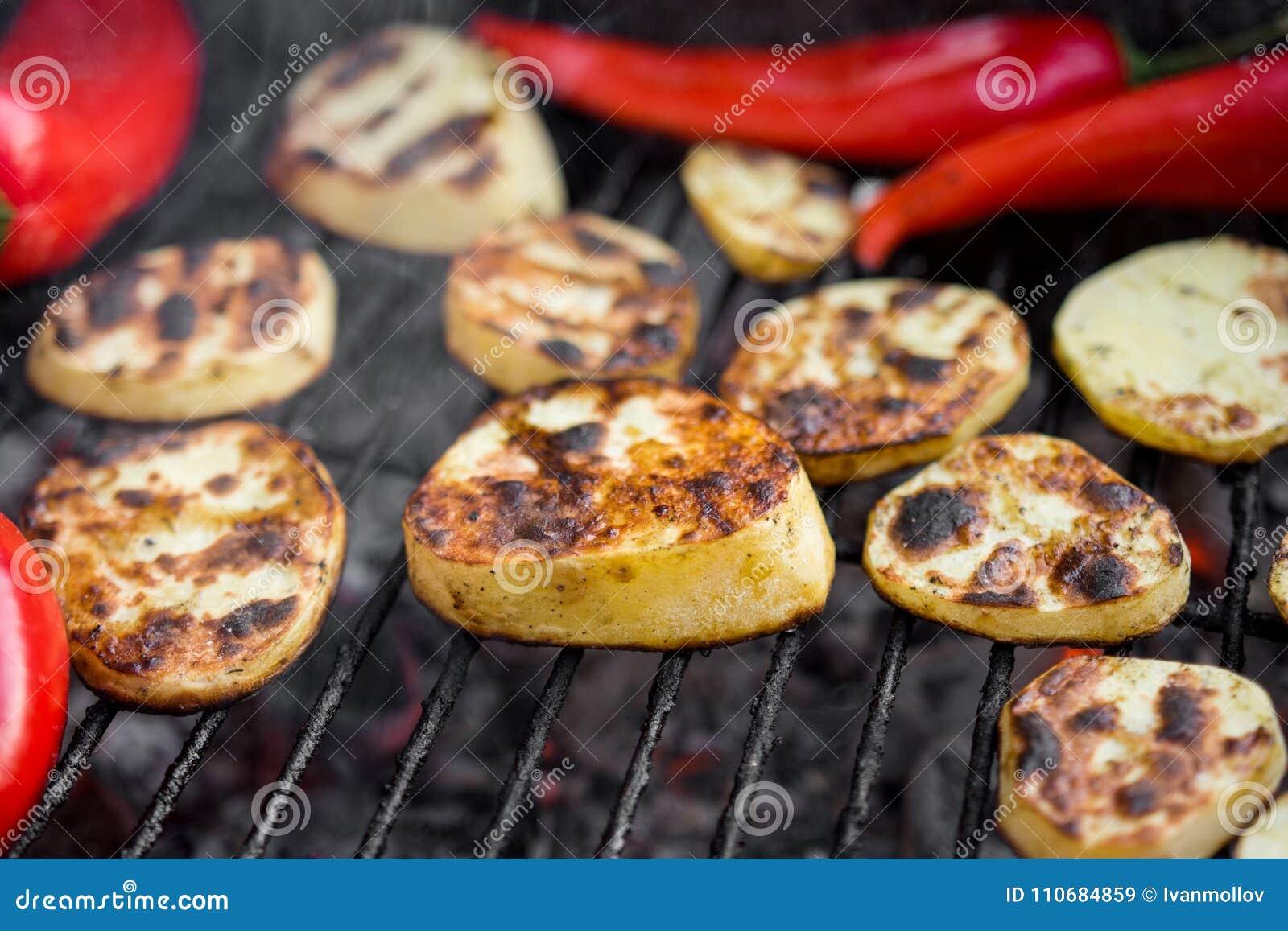 Gril de BBQ avec des morceaux de pommes de terre d une coupe, des poivrons rouges et le blanc de poulet savoureux