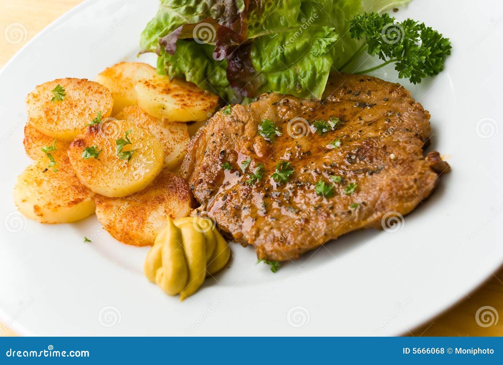 grill mit steaks von schweinefleisch gebratene kartoffeln salat lizenzfreie stockfotos bild. Black Bedroom Furniture Sets. Home Design Ideas