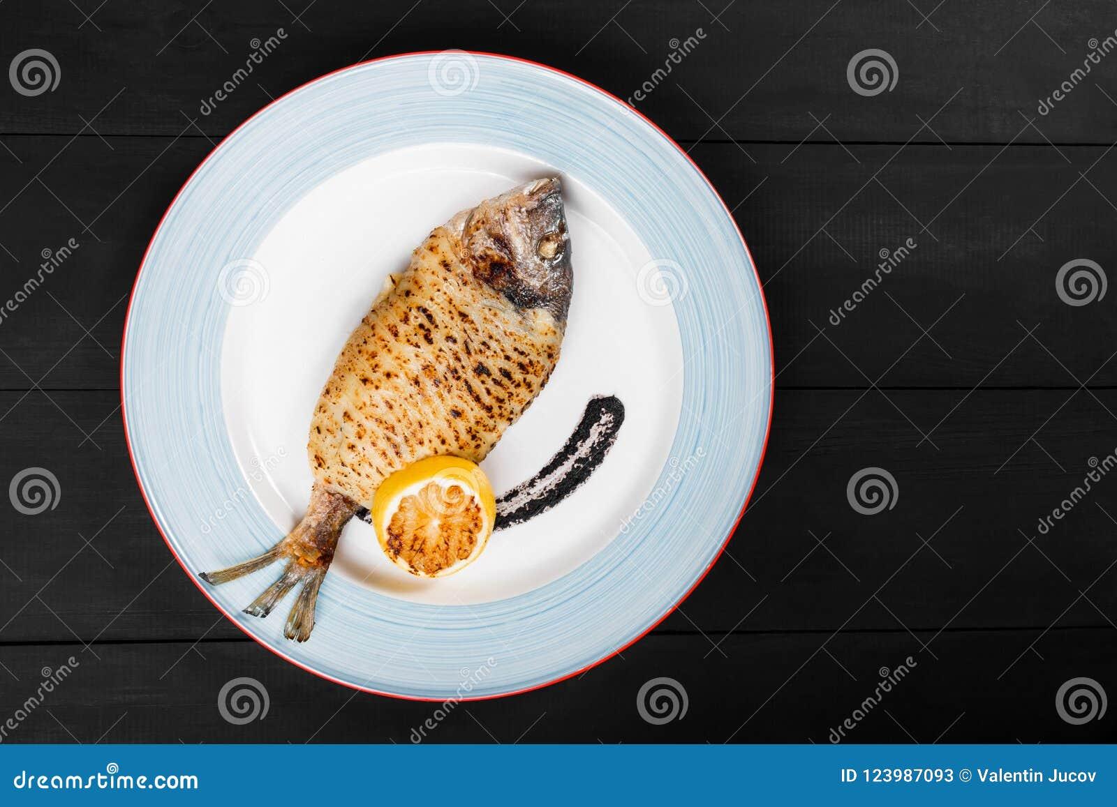 Grillad doradofisk med citron- och tryffelsås på plattan på träbakgrund