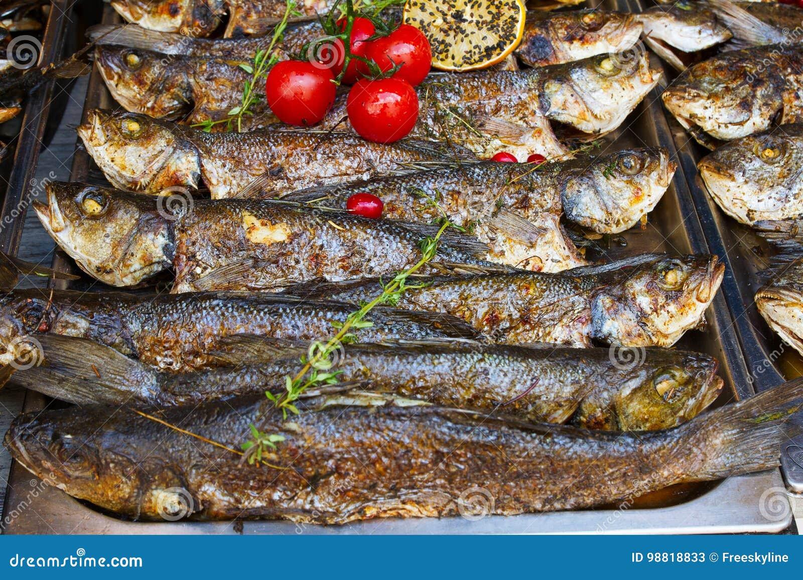 Grillad fiskseabass som tjänas som på matstall på för matfestival för öppet kök internationell händelse av gatamat